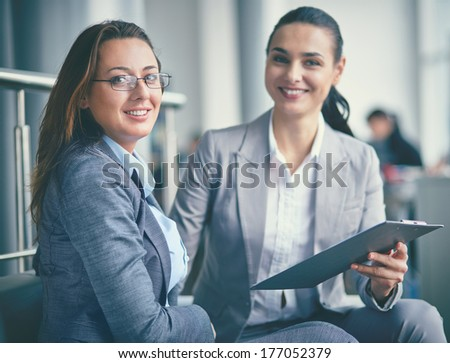 Image of confident businesswoman looking at camera during meeting with co-worker - stock photo