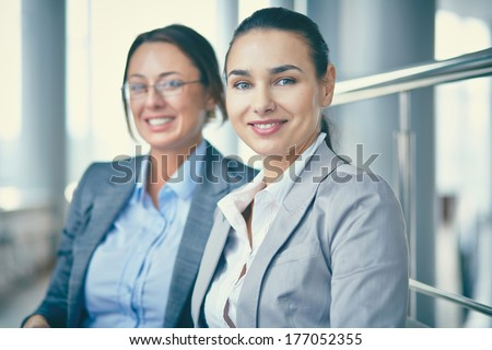 Image of confident businesswomen looking at camera with her colleague behind - stock photo