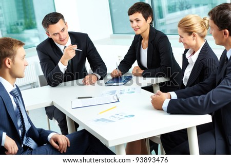 Image of confident colleagues communicating with their boss at meeting