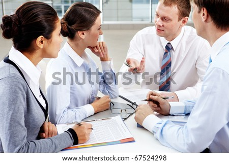 Image of confident colleagues listening to new ideas at meeting