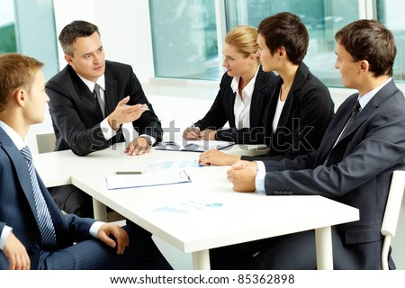 Image of confident colleagues looking at their boss at meeting - stock photo