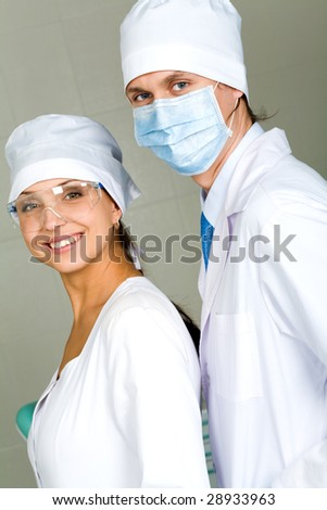 Image of confident doctor with his pretty assistant both looking at camera