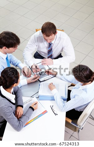 Image of confident employees discussing papers at meeting - stock photo