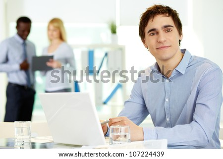 Image of confident leader with laptop looking at camera from workplace - stock photo