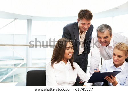 Image of confident manager showing plan to colleagues