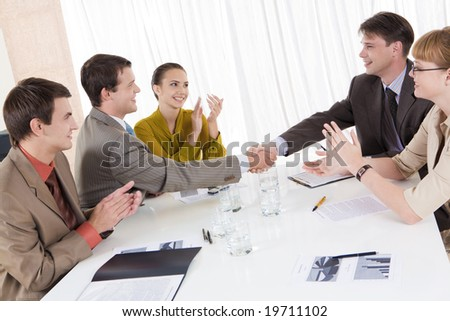 Image of confident partners shaking hands while their colleagues congratulating them - stock photo