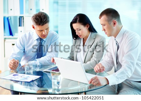 Image of confident partners working with modern communication device at meeting - stock photo