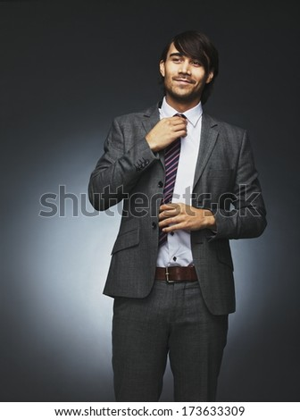 Image of confident young man in business suit looking away and adjusting his necktie. Asian male model against black background. - stock photo