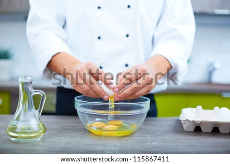 Image of cook hands breaking eggs into bowl
