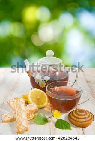 Image of cookies, cup of tea and lemon closeup - stock photo