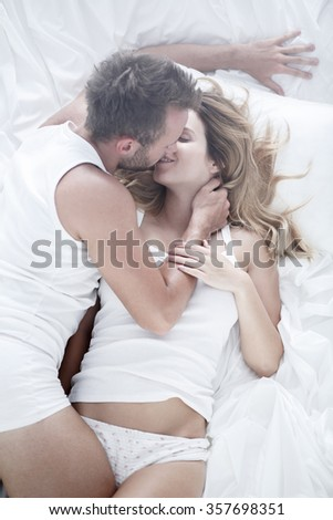 Image of couple during passionate foreplay in bed - stock photo