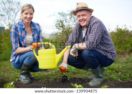 Image of couple of farmers looking at camera in the garden