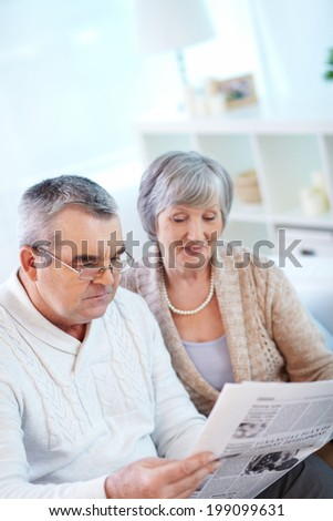 Image of couple of pensioners reading newspaper at home - stock photo