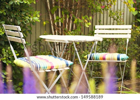 Image of cozy seating area in lush garden. - stock photo