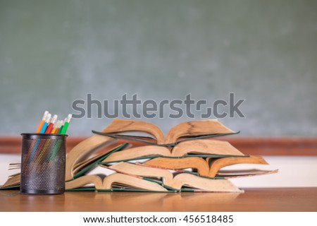 Image of crayons and exercise books against blackboard - stock photo