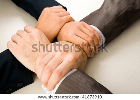 Image of crossed hands of business partners