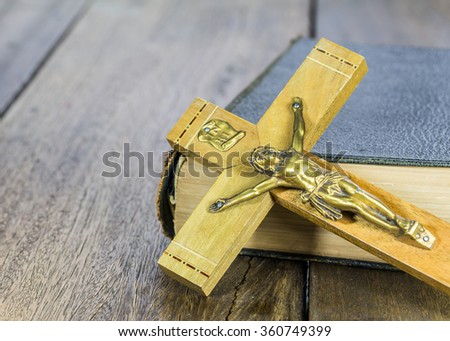 image of crucifix of Jesus Christ with the holy bible on wooden background - stock photo