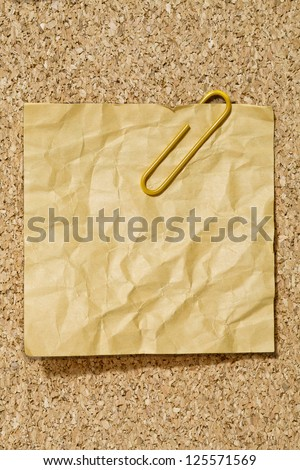 Image of crumpled yellow adhesive paper with paper clip - stock photo