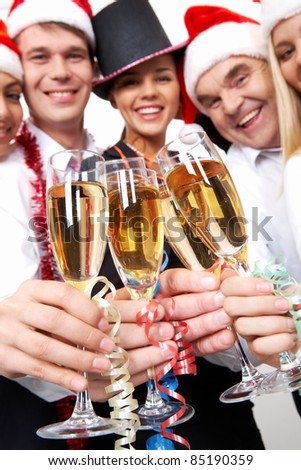Image of crystal glasses full of champagne held by happy business people - stock photo
