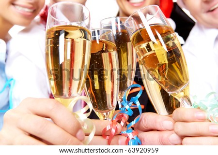 Image of crystal glasses full of champagne held by human hands