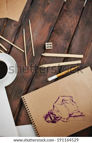 Image of cup of coffee and objects for hand drawing and artist hands with pen over notepad