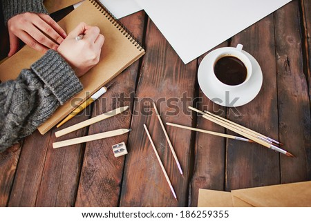 Image of cup of coffee and objects for hand drawing and male hands over notepad - stock photo