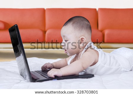 Image of cute baby boy lying on the floor while using laptop computer near the sofa - stock photo