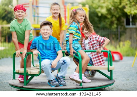 Image of cute friends having fun on carousel outdoors  - stock photo