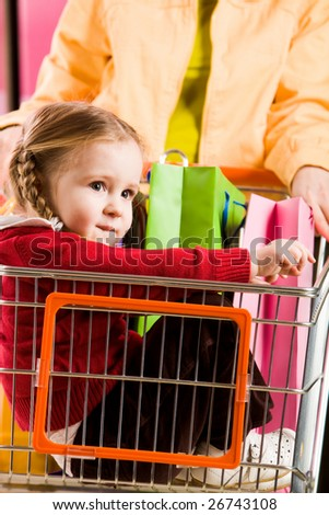 Image of cute girl sitting in handcart while her parents going shopping