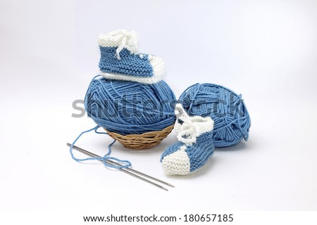 Image of cute little booties with yarn and knitting needles - stock photo
