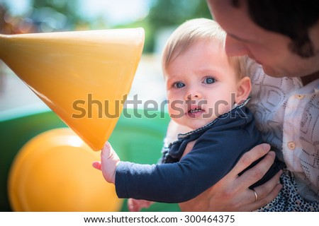 Image of cute little daughter in young dad's hands. Father and baby girl outdoor. Child plays on playground. - stock photo