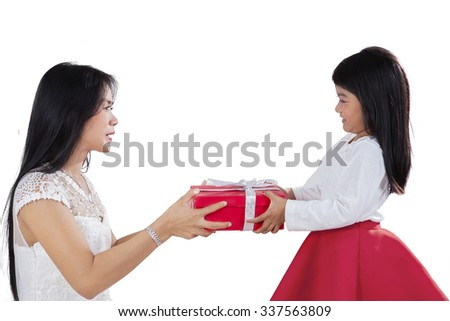 Image of cute little girl smiling at her mother while giving a gift box, isolated on white background - stock photo