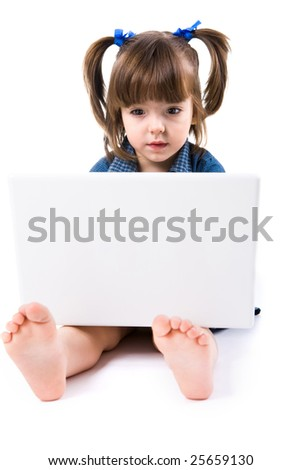 Image of cute preschooler sitting on floor in front of laptop and looking into its screen - stock photo
