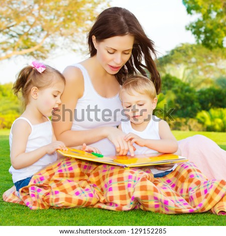 Image of cute young female with two little children read book outdoors, brother and sister with mother learning in the park in spring time, preschool education, day care, happy family concept - stock photo