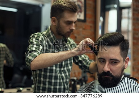Image of cutting hair in a man's barber shop. The working day in Barbershop, stylish hipster customer with beard and mustache stylist cuts. - stock photo