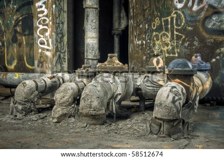 Image of dirty, old pipelines in an industrial abandoned train station. Graffiti damage can be seen in the background.