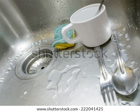 image of  dirty sink with dirty cup,spoon,fork and sponge  - stock photo