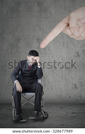 Image of disabled businessman sitting on the wheelchair and looks frustrated with a finger pointing him