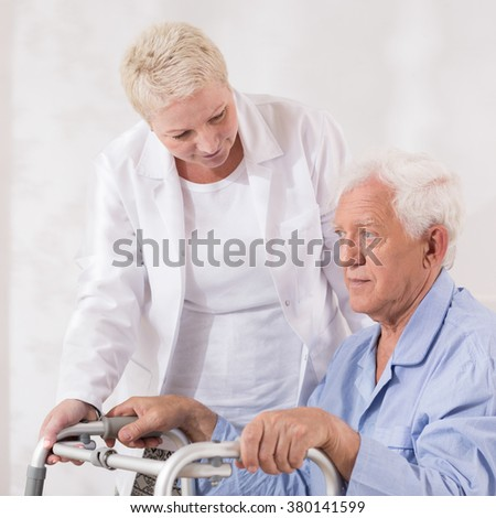 Image of disabled old patient with walking zimmer - stock photo
