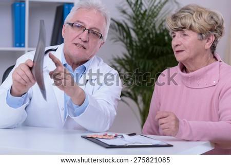 Image of doctor with patient in office - stock photo