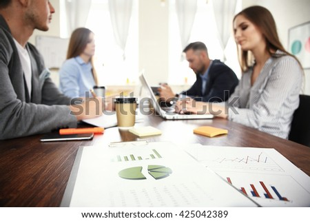 Image of document and pen at workplace and business partners networking on background