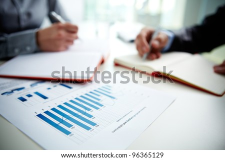 Image of document with charts on background of male and female hands with pens over open notebooks at seminar - stock photo