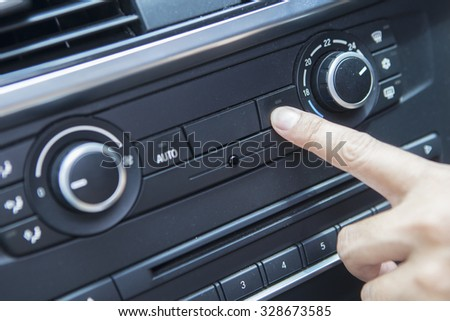 Image of driver hand pushing the air conditioner button in the car