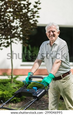 Image of elder gardener with lawn mower