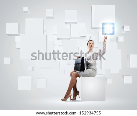 Image of elegant businesswoman sitting on white cube touching media button - stock photo