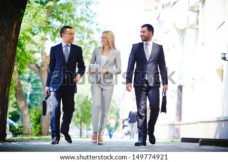 Image of elegant colleagues walking and discussing business matters on the move - stock photo