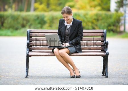 Image of elegant employer sitting on the bench - stock photo