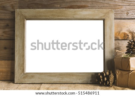 Image of empty frame mockup with rustic christmas gifts.