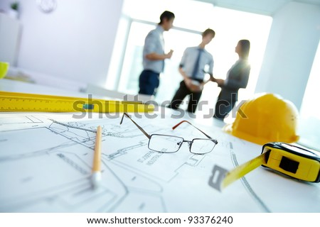 Image of engineering objects on workplace with three partners interacting on background