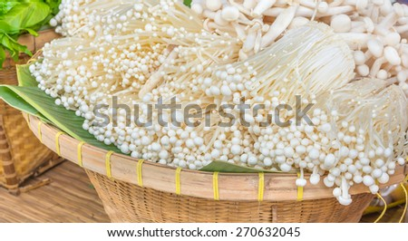image of Enokitake(white mushroom) in wooden basket. - stock photo